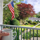 Hand holding coffee cup in foreground porch railing in midground with American flag affixed to post, path leading off in distance